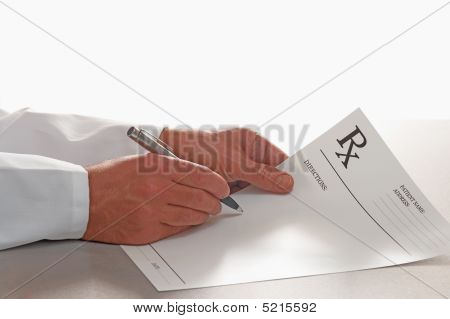 Doctor Writing Out Prescription On Rx Form