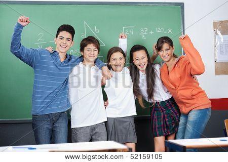 Joyful schoolchildren with hands raised standing together against board in classroom