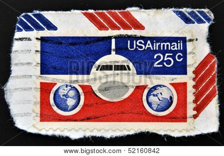 A stamp printed in the USA shows image of an aeroplane and the US flag series