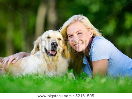 Woman with dog lying on the green grass in the park
