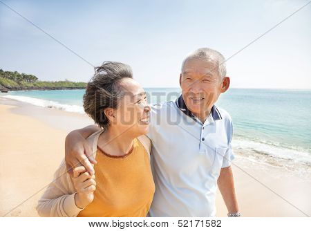 Happy Asian Seniors Walking On The Beach