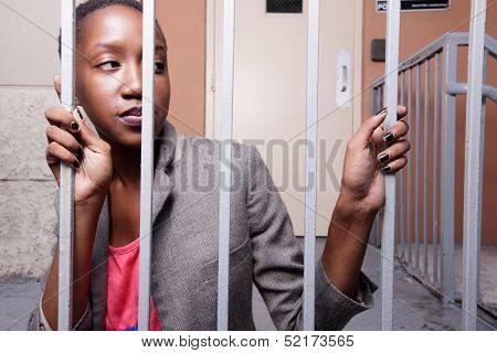 Woman posing behind bars