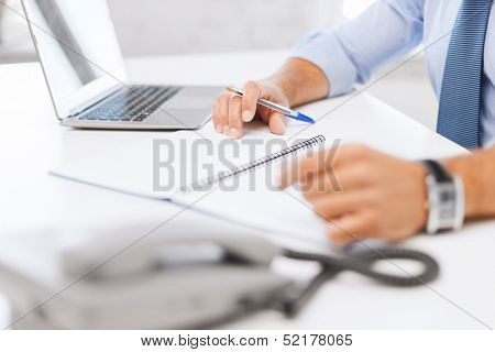 business, office, school and education concept - businessman writing in notebook