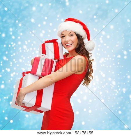 christmas, x-mas, winter, happiness concept - smiling woman in santa helper hat with many gift boxes