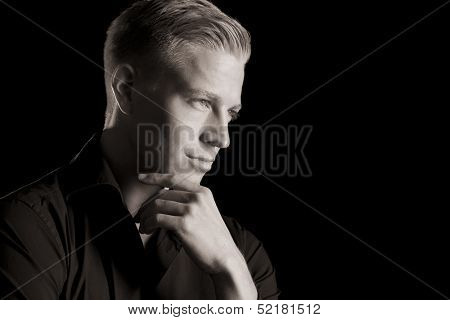 Black and white portrait of smiling handsome man in dark shirt with hand at chin looking aside, low-key, isolated on black background.
