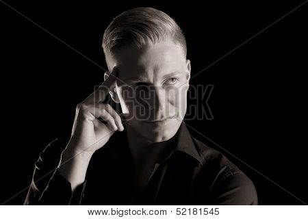 Black and white portrait of confident charming man in dark shirt with hand at temple looking up, low-key, isolated on black background.