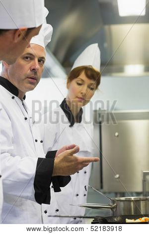 Male mature chef explaining something to a colleague while standing in front of the cooker