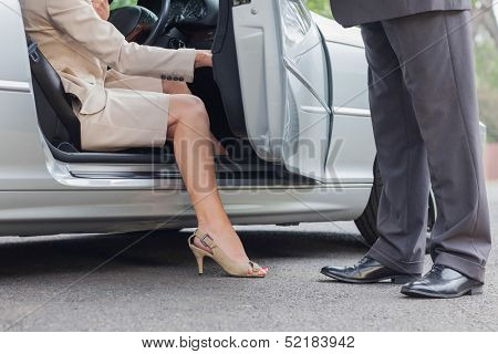 Businesswoman getting off classy cabriolet while businessman holding the door