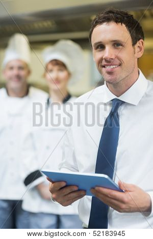 Young restaurant manager holding his tablet  smiling at the camera