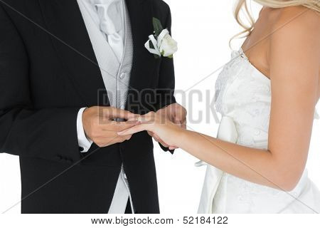 Bridegroom putting the wedding ring on his wife's finger on white background