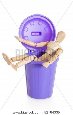 Wooden Mannequin Doll Sitting In Purple Dustbin Can, Isolated