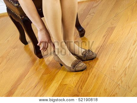 Woman In Stockings Putting On Shoes