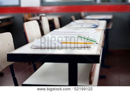 Books and pencil on desk in classroom