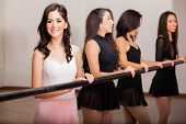 stock photo of ballet barre  - Beautiful ballerinas working out next to a barre in a dance academy - JPG