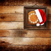 Santa Claus Hat On New Year's Night On The Old Clock Showing Twelve O'clock On The Wooden Background