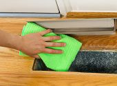 image of floor heating  - Horizontal photo of female hand cleaning using microfiber rag underneath grill plate of heater floor vent with Red Oak Floors and front door in background - JPG