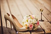stock photo of floral bouquet  - Close up of wedding bouquet and bride shoes - JPG