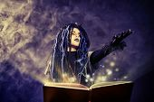 pic of warlock  - Little girl in a costume of witch casts a spell over magic book over dark background - JPG