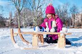 Preschool girl sitting beside sledges and making snowballs