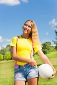 picture of 13 year old  - Happy and smiling 13 years old girl with long blond hair standing in the grass with the ball in the park on sunny summer day with blue sky and white clouds - JPG