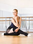 stock photo of ballet barre  - Ballet dancer does exercises sitting on the wooden floor in the classroom with barre and mirrors - JPG