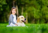 stock photo of labrador  - Little girl sitting on the grass with labrador retriever in the summer park - JPG