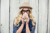 picture of smiling  - Smiling fashionable blonde drinking coffee outdoors on wooden background - JPG