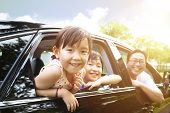 stock photo of car-window  - happy little girl with family sitting in the car - JPG