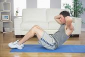 image of crunch  - Fit handsome man doing sit ups in bright living room - JPG