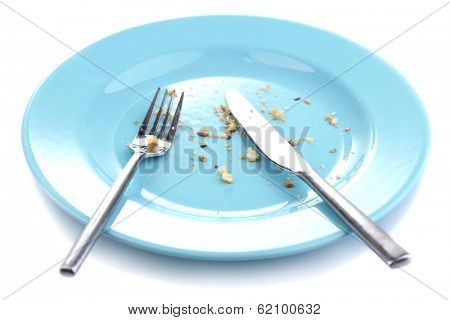 Plate with crumbs and used fork and knife, close-up, on white background