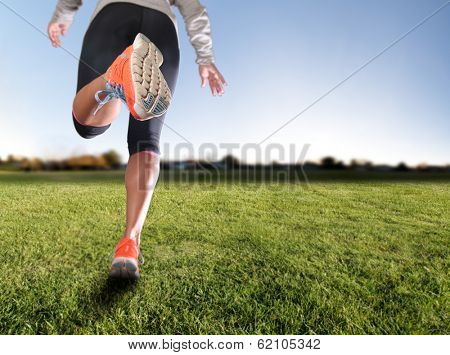 an athletic pair of legs on grass during sunrise or sunset