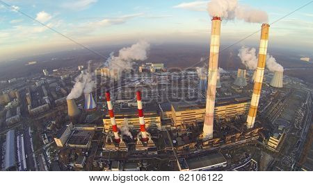 Territory of power plant with chimneys with smoke at winter. Aerial view
