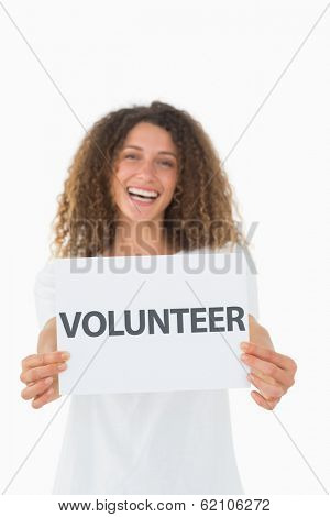 Smiling volunteer showing a poster on white background