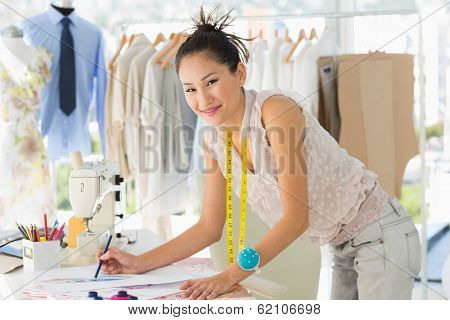 Side view of a young female fashion designer working on her designs in the studio