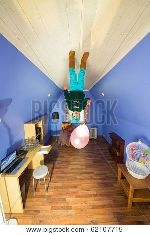 Little boy with air balloon standing on the ceiling in the room