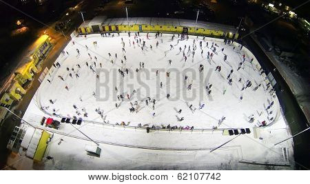 Many people skate on big white slippery rink in winter night. Aerial view