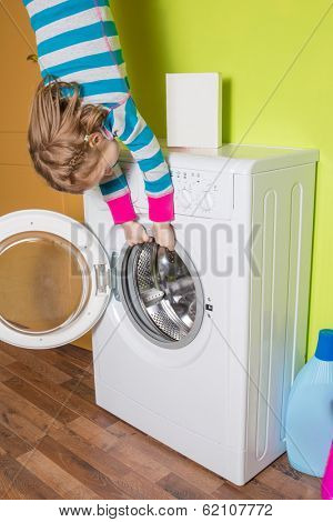 Girl hanging upside down holding a washing machine at inverted house