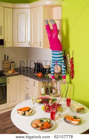 Little girl upside down holds a chair in the kitchen with table and dishes