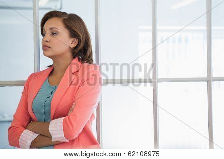 Serious young businesswoman looking away at a bright office