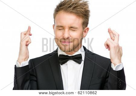 Half-length portrait of manager with fingers crossed and eyes closed, isolated on white