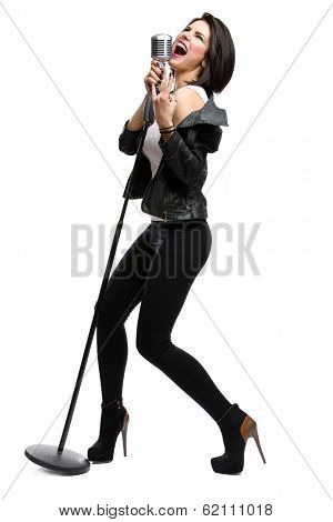 Full-length portrait of rock singer wearing leather jacket and keeping static microphone, isolated on white. Concept of rock music and rave