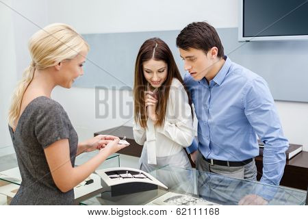 Salesperson helps couple to choose jewelry at jeweler's shop. Concept of wealth and luxurious life