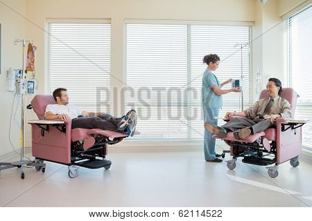 Full length of female nurse adjusting IV machine while patients reclining on chair in hospital room