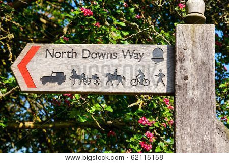 Wooden sign post pointing to the North Downs Way National Trail in southern England