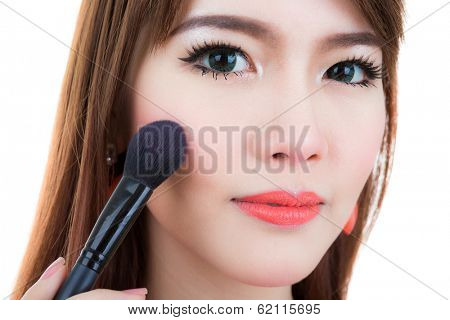 Young woman Make up with Cosmetic Powder Brush