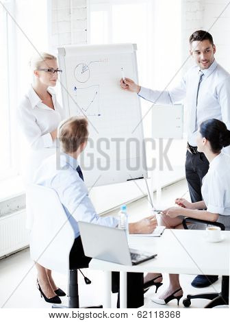 business concept - young businessman pointing at graph on flip board in office