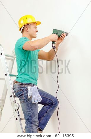 repair, building and home concept - smiling man in yellow protective helmet with electric drill making hole in wall