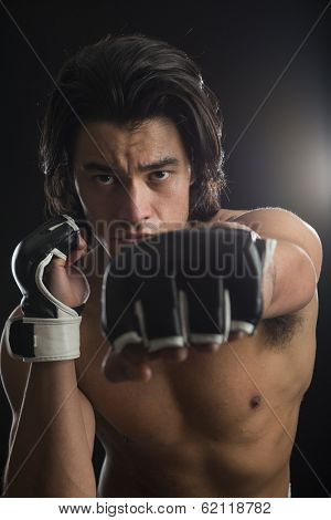 Bare chested young Malaysian boxer punching in the direction of the camera with fingerless gloves