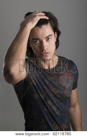 Portrait of handsome Malaysian man wearing flowery top with hands on hair