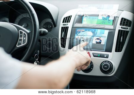 transportation and vehicle concept - man using car control panel to read news